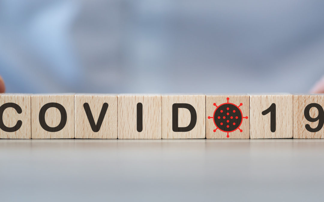 Scrabble board pieces that spell out COVID-19