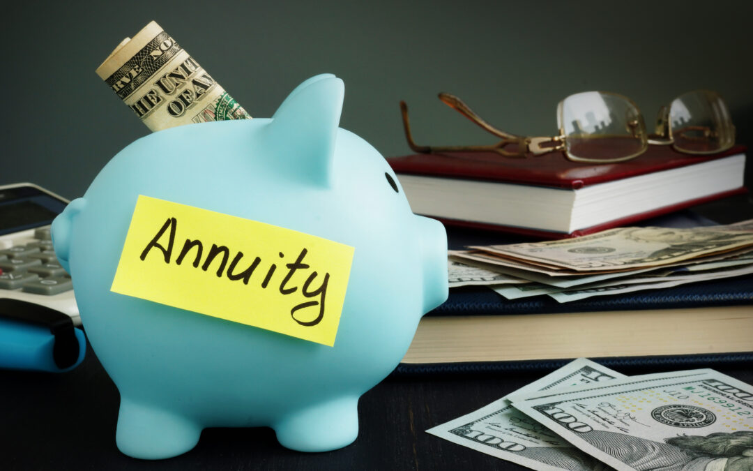 Annuity written on a yellow post-it and stuck to a blue piggy bank sitting in front of stack of books