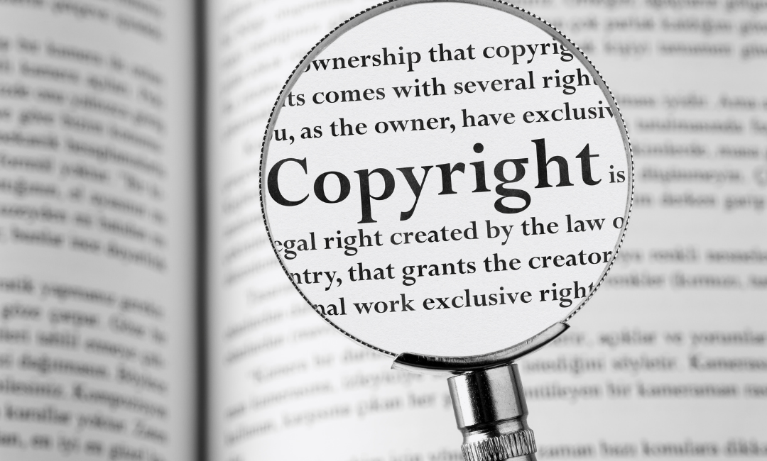 Magnifying glass over a dictionary entry of the word copyright it protects works of art and more