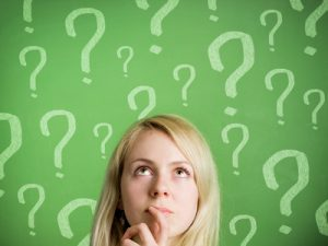 Thinking woman in front of blackboard with question marks